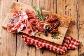 Cold Meat Plate And Sun-dried Tomatoes On Wooden Background