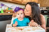 Woman Kisses Baby In Kitchen
