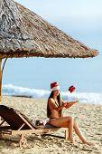 santa girl on the beach with christmas gift
