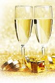 Champagne in glasses and gift boxes on golden background
