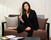 Woman in bathrobe relaxing with glass of champagne in hotel room