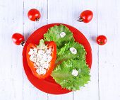 Stuffed pepper with lettuce on plate and tomatoes on wooden background