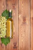 White wine bottle and bunch of white grapes on wooden table background with copy space