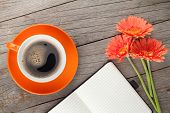Blank notepad, coffee cup and orange gerbera flowers on wooden table background