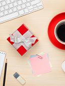 Red gift box on office table. View from above