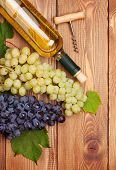 White wine bottle and bunch of grapes on wooden table background