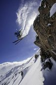 Skier jumping against blue sky.