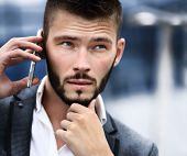 Young business man talking on cell phone near modern office