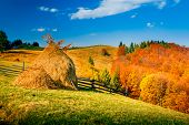 Autumn landscape in a mountain village. Two stack of dry hay. Beautiful evening clouds. Carpathian mountains, Ukraine, Europe