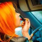 Girl Painting Her Lips Doing Makeup While Driving The Car.