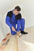 Craftsman putting wooden floor in room