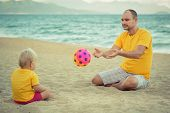 Baby and father on the tropical beach playing toy ball