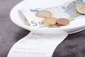 stock photo of tariff  - Tip and bill on a gray restaurant table - JPG