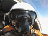 pic of aerialist  - The military pilot in the plane in a helmet in dark blue overalls against the blue sky - JPG