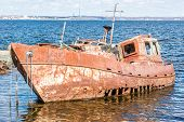 image of shipwreck  - Front and side view of very rusty shipwreck with big holes in the hull - JPG