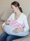 stock photo of breastfeeding  - Happy mother breastfeeding her newborn in room indoor - JPG