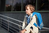 stock photo of schoolboys  - Portrait of serious schoolboy with backpack outdoor - JPG