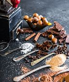 stock photo of chocolate spoon  - Sweet spices in the spoons and chocolate on a table black - JPG