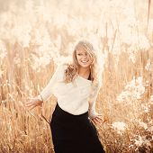 stock photo of pullovers  - Portrait of a beautiful young blonde girl in a field in white pullover smiling concept of beauty and health - JPG