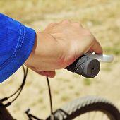 foto of dirt-bike  - closeup of a young man riding a mountain bike on a dirt road - JPG