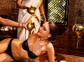 picture of ayurveda  - Young woman having ayurveda spa treatment - JPG
