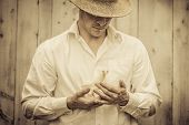image of baby cowboy  - Farmer Holding a Baby Turkey in its hand - JPG
