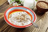 stock photo of porridge  - Buckwheat porridge with milk in the bowl on the table - JPG