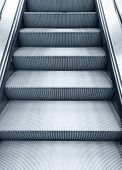 picture of escalator  - Shining metal escalator moving up vertical monochrome photo with blue toning filter effect - JPG