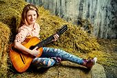 image of denim jeans  - Beautiful girl teenager in shirt and torn jeans playing guitar sitting on hay - JPG