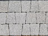 picture of trapezoid  - beautiful wall of artificial light gray stones in the shape of a trapezoid made of concrete for finishing the exterior facades of buildings and tracks - JPG