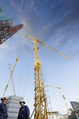 picture of construction crane  - two building workers with construction cranes at sunset - JPG