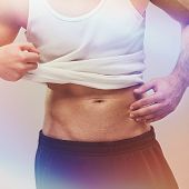 picture of abdominal muscle man  - Closeup of unrecognizable fit handsome young man in white tank top showing abdominal muscles - JPG