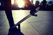 image of skateboarding  - woman skateboarder legs skateboarding at sunrise city - JPG