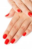 stock photo of fingernail  - Woman with beautiful manicured red fingernails gracefully crossing her hands to display them to the viewer on a white background in a fashion glamour and beauty concept - JPG