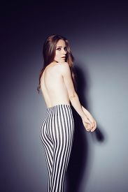 stock photo of wet pants  - Portrait of a beautiful young blonde woman in a studio in striped pants - JPG