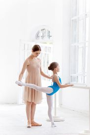 foto of ballet barre  - The little ballerina in tutu with personal classic ballet teacher in dance studio posing at ballet barre on a white studio background - JPG