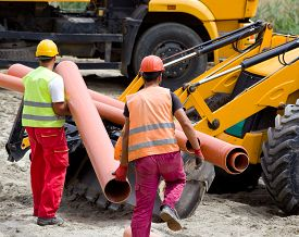 image of bulldozers  - Construction workers in safety cloths carrying pipes and loading bulldozer for transportation at building site - JPG