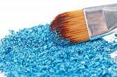Cepillo de maquillaje con azul aplastó la sombra de ojos, aislado en blanco Macro