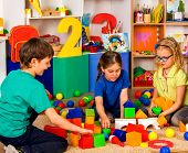 Children playing in kids cubes indoor. Lesson in primary school. Two girl and boy together play. Kin poster