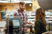 Photo of happy young man standing in supermarket shop near cashiers desk holding credit card. Looki poster