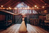 Stylish Groom And Happy Bride Hugging Under Retro Bulbs Lights In Wooden Barn. Rustic Wedding Concep poster