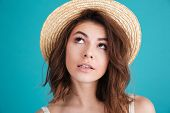 Close up portrait of a thoughtful young woman in straw hat wondering and looking away isolated over  poster