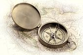 vintage pocket brass compass over old map, retro hand tinted opalotype processing poster