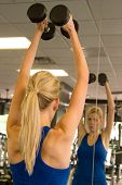 picture of lifting weight  - Beautiful blond woman lifting weights while looking at image in mirror in a fitness center - JPG