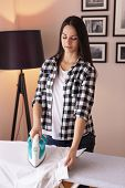 Woman Holding The Iron, Ironing Washed, Wrinkled Clothes On The Ironing Board poster