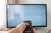 Hand With Tv Remote Control In Front Of The Screen With White Noise On It - Tuning The Television Ch poster