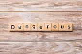 Dangerous Word Written On Wood Block. Dangerous Text On Wooden Table For Your Desing, Concept poster