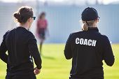Back View Of Female Sport Coach And Her Assistant In Black Coach Shirt At An Outdoor Sport Field, Wa poster