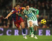 BARCELONA - JAN 12: Puyol of Barcelona fight with Molina of Betis during the match between FC Barcelona and Real Betis at the Nou Camp Stadium on January 12, 2011 in Barcelona, Spain