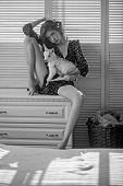 Girl With Baby Sheep On Chest Of Drawers. Young Woman Cuddle Small Lamb In Bedroom. Pet, Domestic An poster